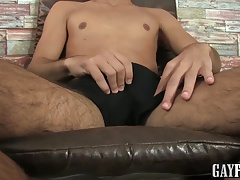 Horny muscled twink wanks his uncut cock while sitting down
